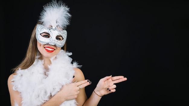 白い背景で身振りで示すカーニバルマスクを着て笑顔の女性の肖像画 無料写真