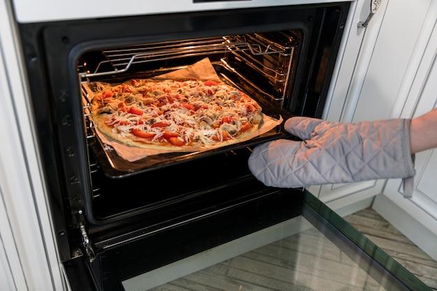 Человек кладет пиццу в духовку Бесплатные Фотографии