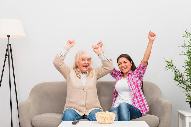 興奮してシニアの母と娘のテレビを見ながら彼らの腕を上げるソファーに座っていた 無料写真