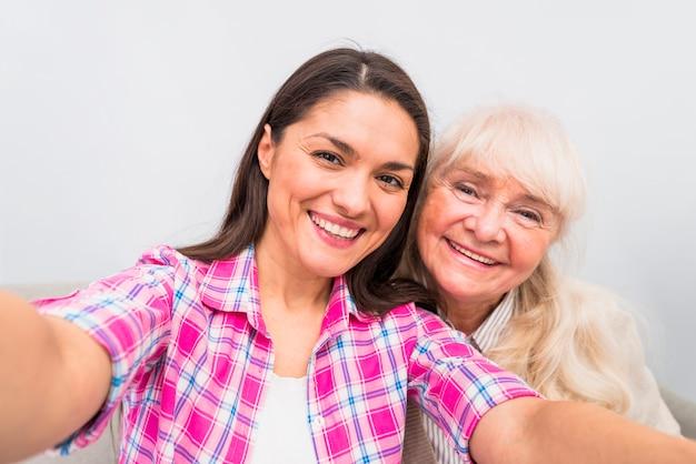 白い背景に対してセルフポートレートを取る彼女の娘と一緒に陽気な年配の女性 無料写真