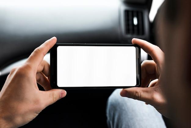 彼の携帯電話の白い画面表示を見ている男の手のクローズアップ 無料写真