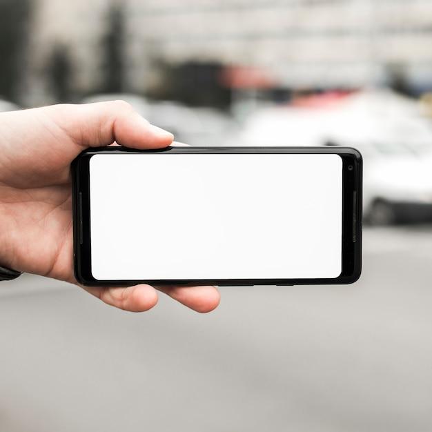 空白の白い画面を示す携帯電話を持つ手のクローズアップ 無料写真