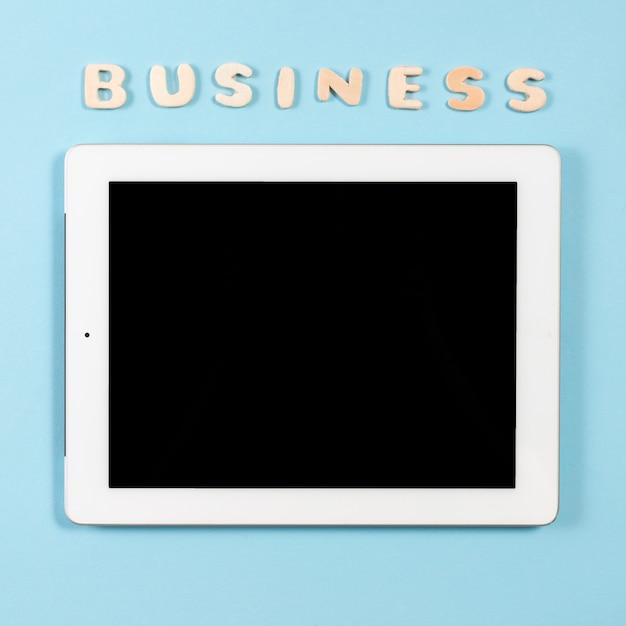 青い背景にデジタルタブレットの上に木製の単語ビジネス 無料写真