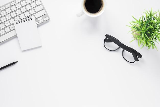 Макет рабочего пространства для домашнего офиса со спиральным блокнотом; клавиатура; кофе; очки и растения Бесплатные Фотографии