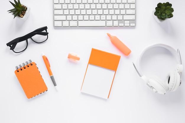 事務用品と白いオフィスデスクトップの平面図 無料写真