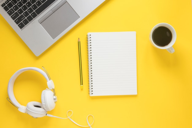 Ноутбук; белые наушники; чашка кофе; карандаш и спиральный блокнот на желтом фоне Бесплатные Фотографии