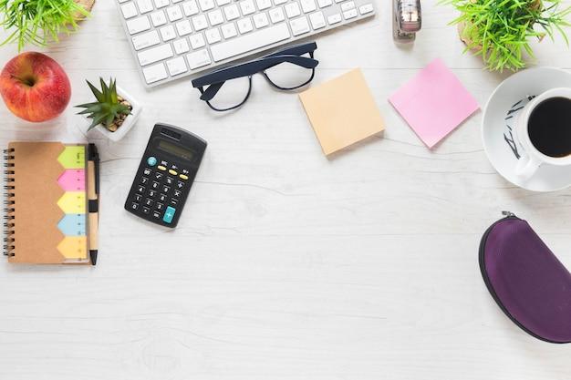 木製の机の上の電卓と事務用品とアップル 無料写真