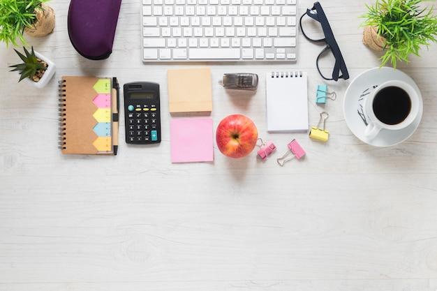 白い木製の机の上のオフィス文房具とアップルとコーヒーカップのトップビュー 無料写真