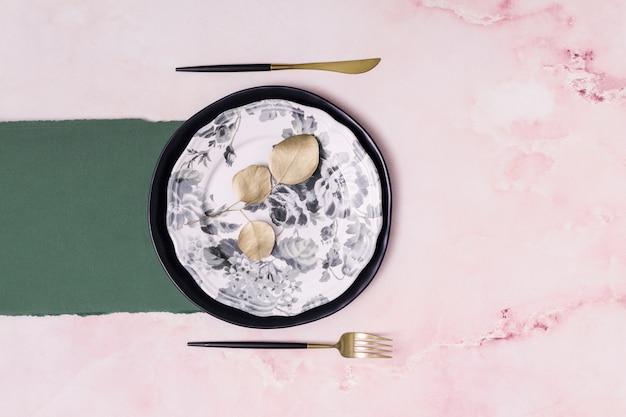 紙とカトラリーの近くの皿に乾燥葉のセット 無料写真
