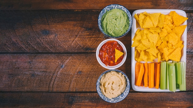 メキシコのナチョスチップを使ったボウルのソース各種。木製のテーブルの上のトレイにニンジンとセロリの茎 無料写真