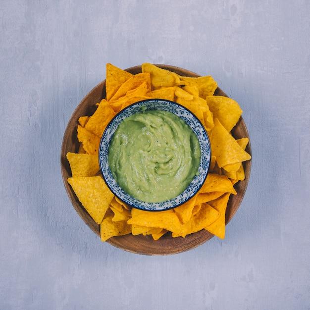 具体的な背景の上のコンテナーでワカモレとメキシコのナチョスチップ 無料写真