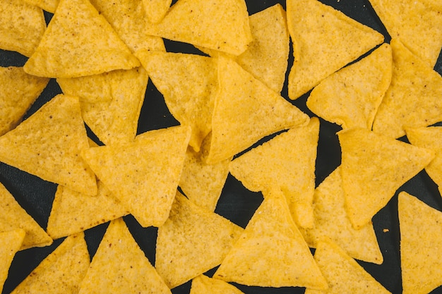 黒の背景上の黄色のメキシコのナチョスチップ 無料写真