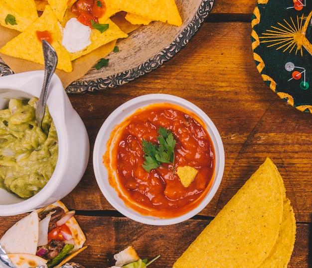 サルサソースグアカモーレ;おいしいメキシコのナチョス。トルティーヤと木製のテーブルの上のメキシコのタコスをラップ 無料写真
