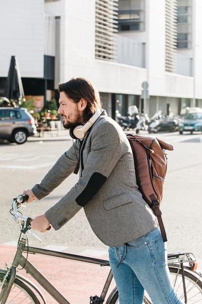 彼の自転車と道路上に立っているバックパックを運ぶ男の側面図 無料写真