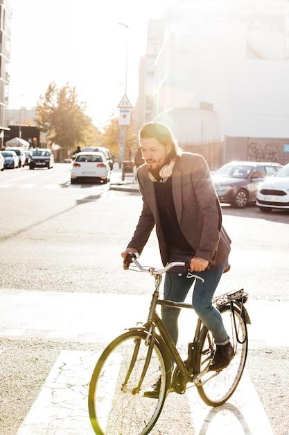 日光の下で都市道路上の男乗馬自転車の肖像画 無料写真