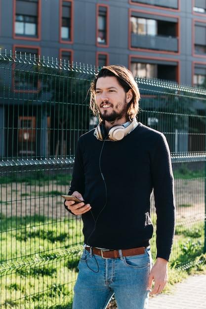 フェンスの近くに立っている彼の首の周りのヘッドフォンに接続されている携帯電話を持つハンサムな若い男性 無料写真