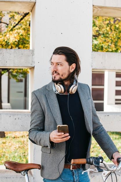 Портрет мужчины, стоящего возле стены с велосипедом и мобильным телефоном Бесплатные Фотографии