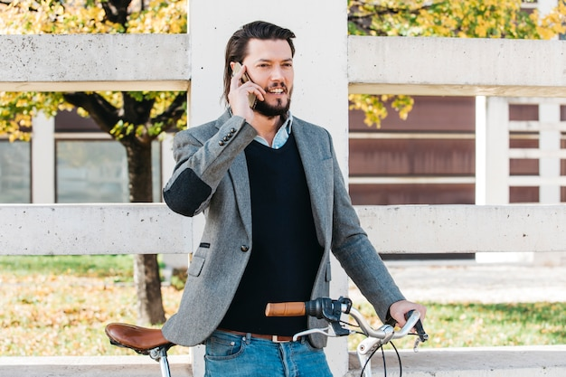 Улыбающийся молодой человек разговаривает по мобильному телефону, стоя с велосипедом в парке Бесплатные Фотографии