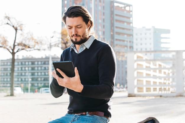 若い男が市の建物に対してベンチに座っているスマートフォンを使用して 無料写真