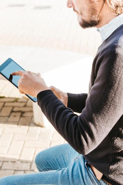 Крупным планом человека, касаясь сенсорного экрана смартфона на открытом воздухе Бесплатные Фотографии