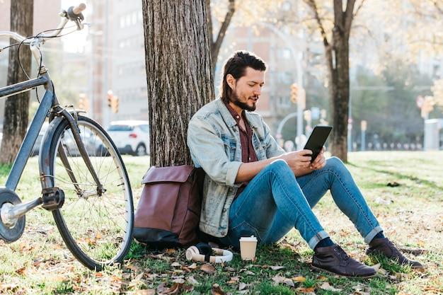 持ち帰り用のコーヒー紙コップが付いている公園で携帯電話を使用してツリーの下に座っている若い男 無料写真