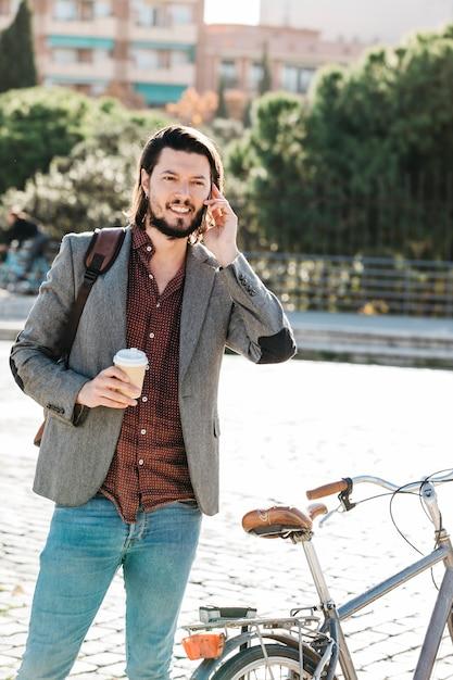 公園で携帯電話で話しているテイクアウトのコーヒーカップを持って笑顔のハンサムな男 無料写真
