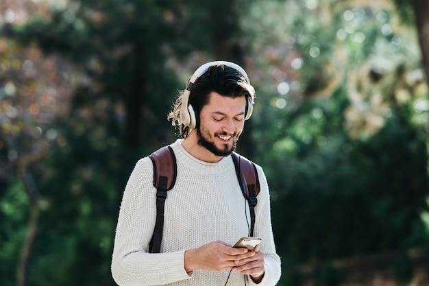 公園でヘッドフォンで音楽を聴くために電話を使用して笑顔の若い男 無料写真