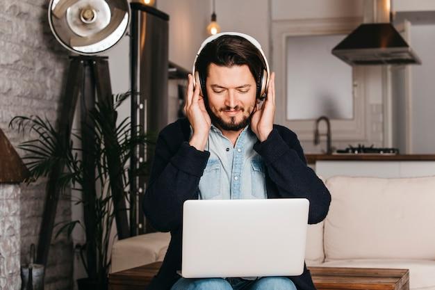 台所に座ってデジタルタブレットを見てヘッドフォンを着た男 無料写真