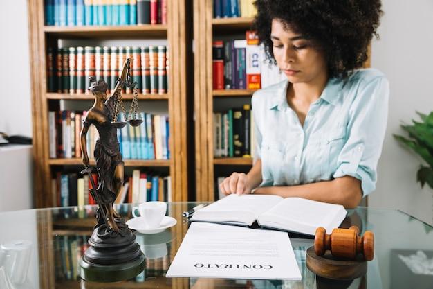 カップとドキュメントのテーブルで本を持つアフリカ系アメリカ人の若い女性 無料写真