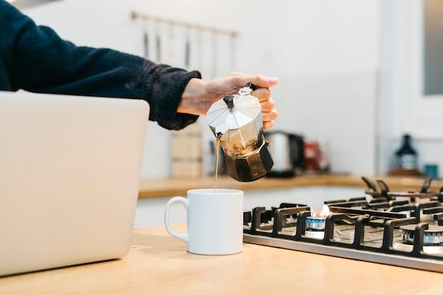 ガスコンロの近く白いマグカップでコーヒーを注ぐ人の手のクローズアップ 無料写真