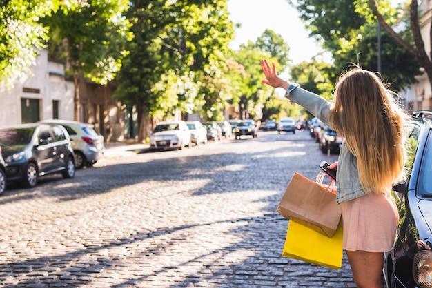 タクシーをキャッチする買い物袋を持つ女性 無料写真