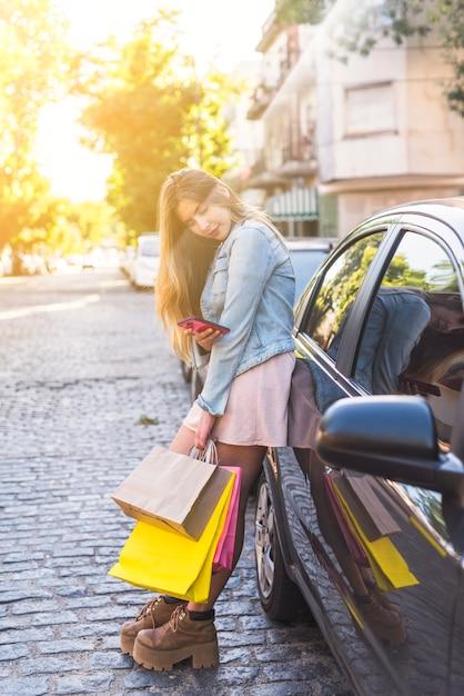車でスマートフォンを使用して買い物袋を持つ若い女 無料写真