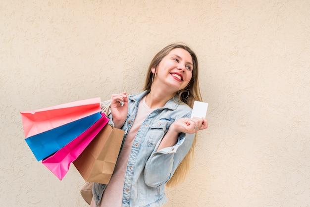 買い物袋とクレジットカードの壁に立っている幸せな女 無料写真