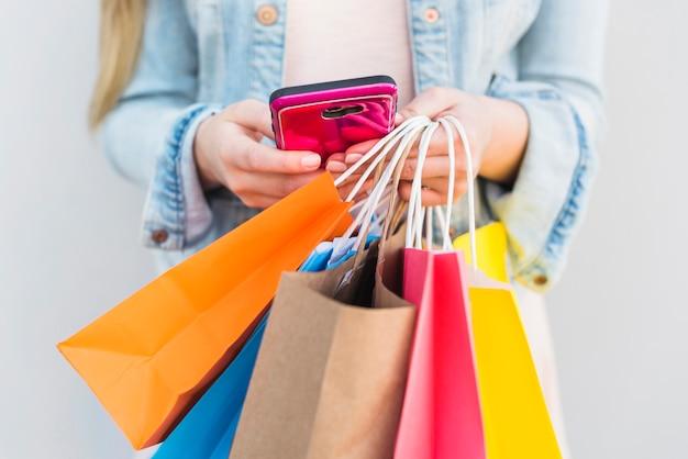 スマートフォンを使用して明るい買い物袋を持つ女性 無料写真