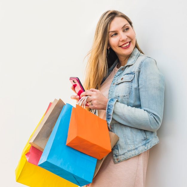 スマートフォンを使用して明るい買い物袋を持つきれいな女性 無料写真