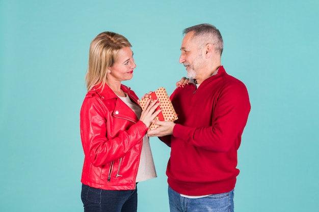 年配の男性が青い背景に立っている彼の妻にプレゼントを与える 無料写真