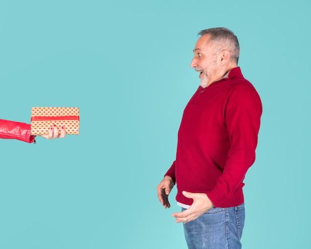 Удивленный зрелый человек, глядя на женскую руку, держа упакованную подарочную коробку на бирюзовом фоне Бесплатные Фотографии