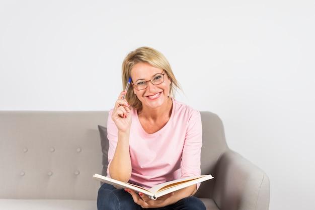 ペンと白い背景に対して本を持ってソファーに座っていた金髪の成熟した女性の笑顔 無料写真