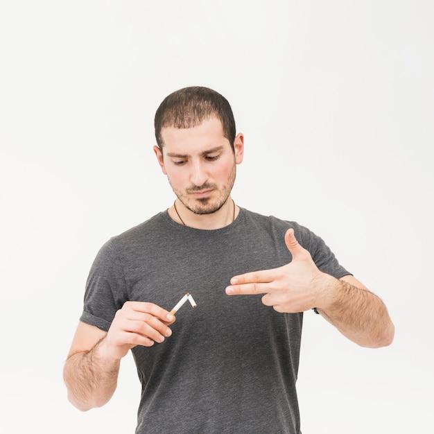 Портрет человека, держащего сломанную сигарету, делающего жест пистолета на белом фоне Бесплатные Фотографии