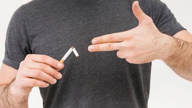 Средняя часть человека показывает жест пистолета в сторону сломанной сигареты Бесплатные Фотографии