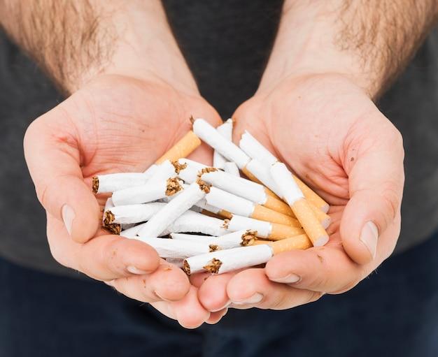 Крупный план мужской руки, показывая сломанные сигареты Бесплатные Фотографии