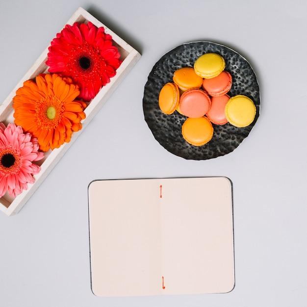 クッキーとテーブルの上の明るい花のノート 無料写真