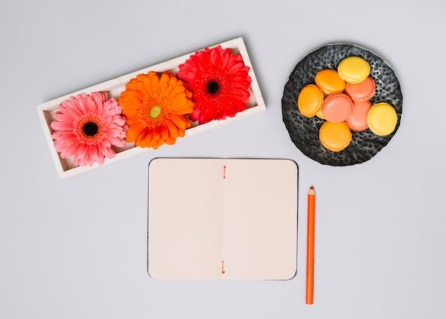 クッキーと白いテーブルの上の明るい花のノート 無料写真