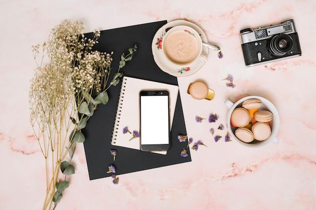 クッキー、カメラ、テーブルの上のコーヒーカップを持つスマートフォン 無料写真