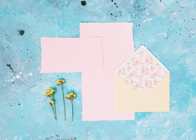 Желтые цветочные ветви с открытым конвертом на синем столе Бесплатные Фотографии