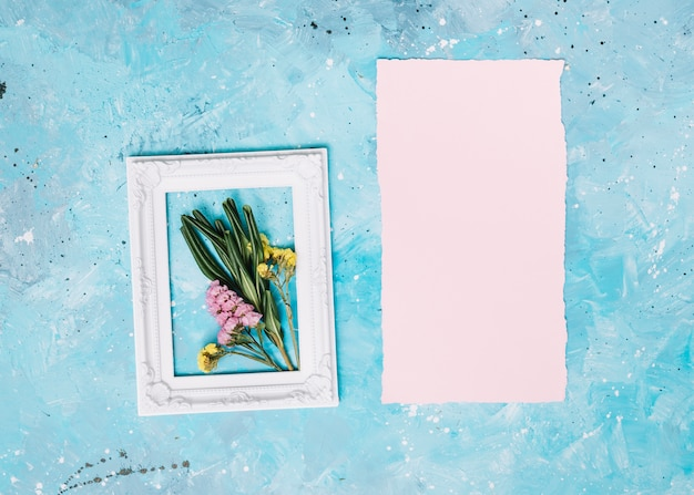 Маленькие цветы ветви в рамке с чистого листа на столе Бесплатные Фотографии
