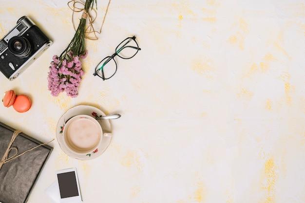 花の花束、カメラとテーブルの上のグラスとコーヒーカップ 無料写真
