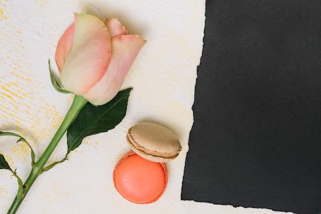 クッキーと黒い紙のテーブルの上のバラの花 無料写真