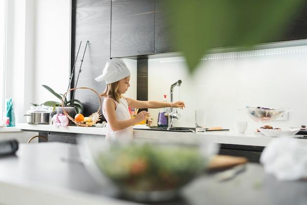 自宅の蛇口の下で彼女の手を洗うシェフの帽子を持つ少女 無料写真
