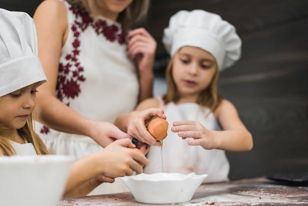 食べ物を準備しながらボウルに卵を割れの女の子 無料写真